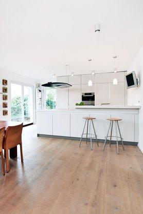 Moderne, große Küche ganz in Weiß mit langer Thresen